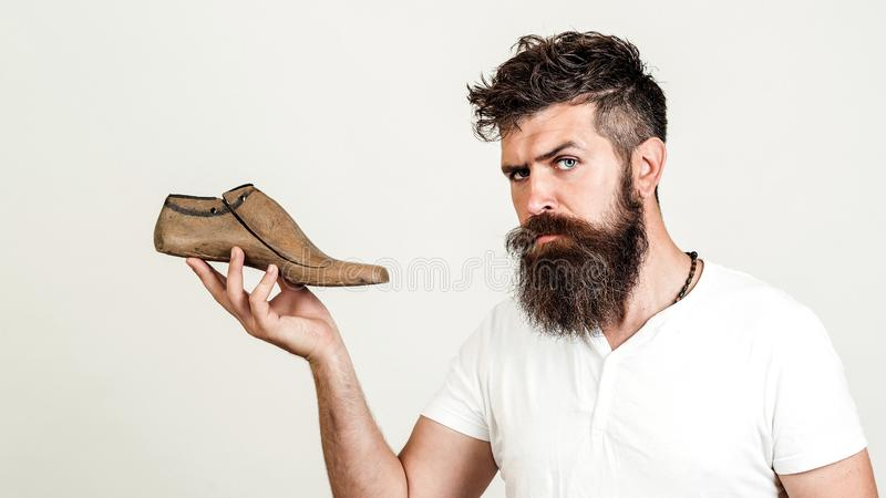 Handsome bearded shoemaker on white background. Bearded man holding last shoe. Looking at camera. Serious young cobbler sets up royalty free stock image