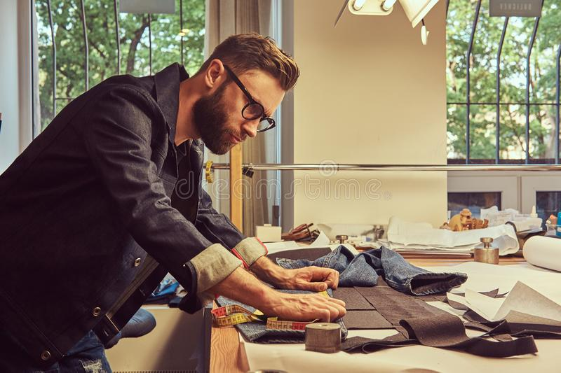 Handsome bearded tailor makes measurements of jeans cloth samples at sewing workshop. Handsome bearded tailor makes measurements of jeans cloth samples at a stock photography