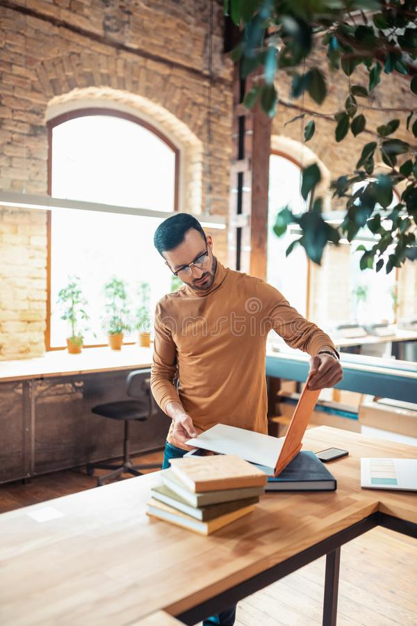 Handsome bearded writer standing in light spacious printing office stock photo