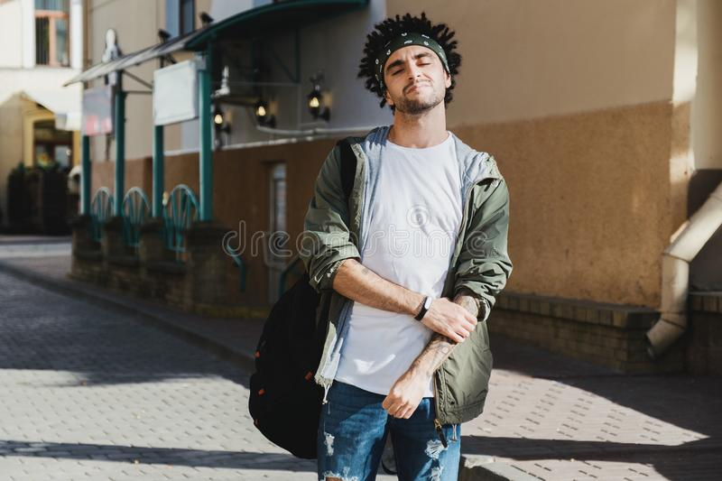 Handsome bearded young man with dreadlocks hairstyle dressed fashionable clothes enjoying life. Autumn fashion outfit, outdoor royalty free stock photo