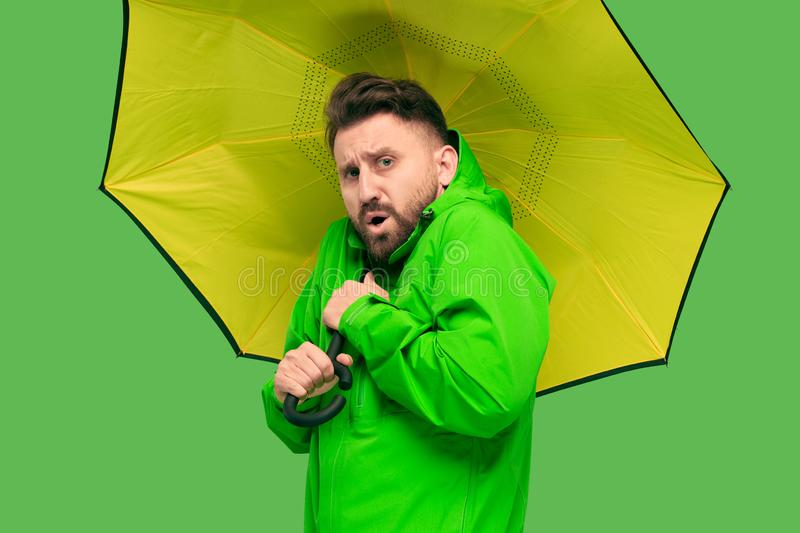 Handsome bearded young man holding umbrella and looking at camera isolated on white stock photography