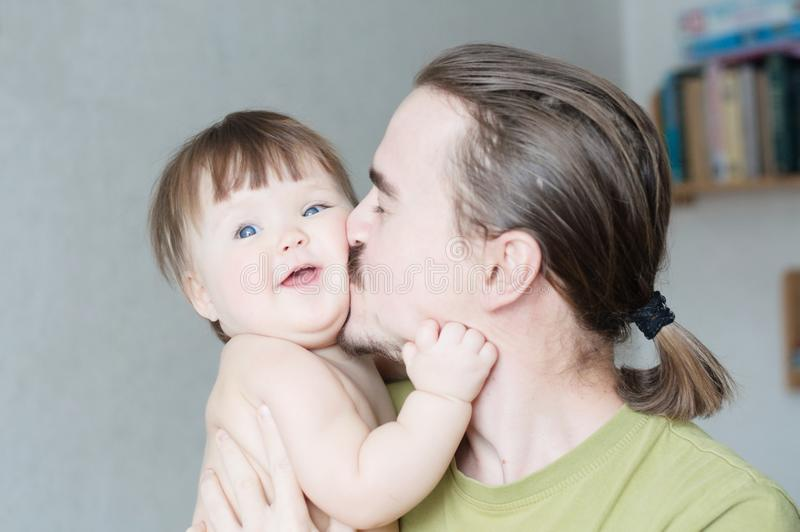 Handsome bearded young man kissing infant little girl. Happy smiling father and baby daughter portrait royalty free stock images