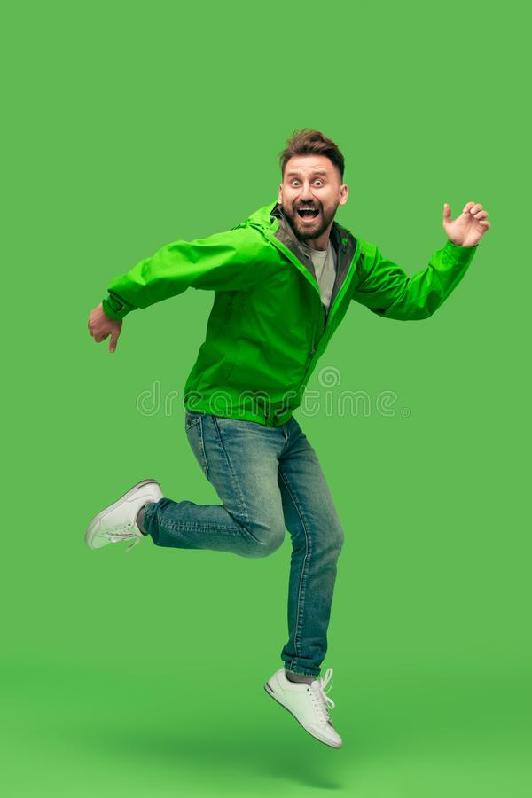 Handsome bearded young man running isolated on green stock photography