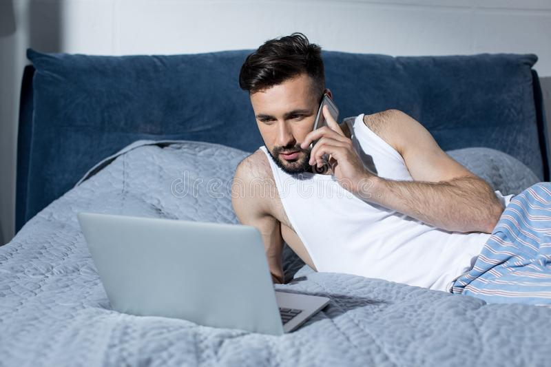 Handsome bearded young man talking on smartphone and using laptop. In bed stock images