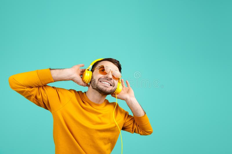 Handsome bearded young man wearing yellow sunglasses listening to music with yellow headphones on cyan background. stock photo