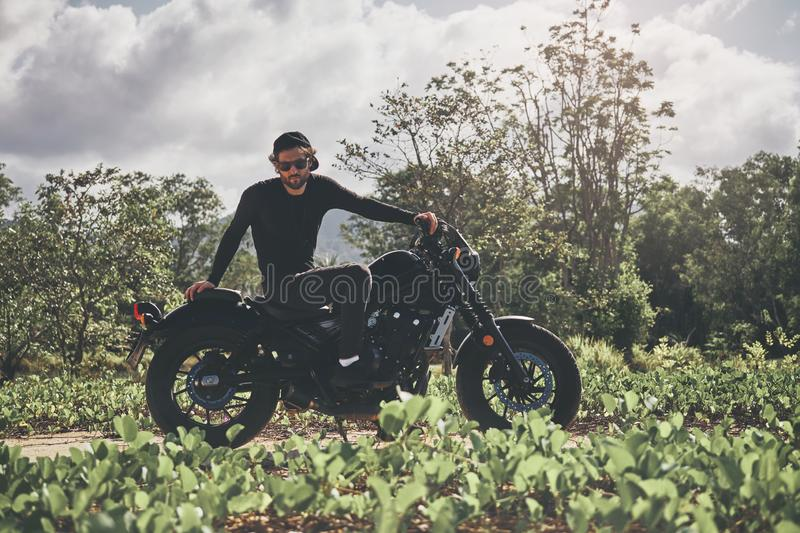 Handsome biker man in black wear sit on classic style cafe racer motorcycle. custom made motorcycle royalty free stock photos