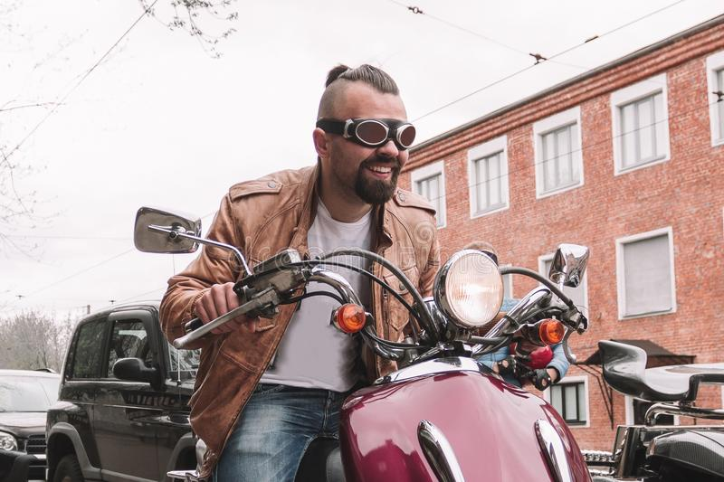 Handsome biker man sitting on his motorcycle. City life stock photo