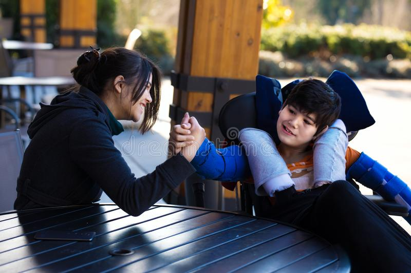 Disabled boy in wheelchair arm wrestling with caregiver outdoors. Handsome biracial Asian Caucasian disabled boy in wheelchair playing arm wrestling with sister stock image