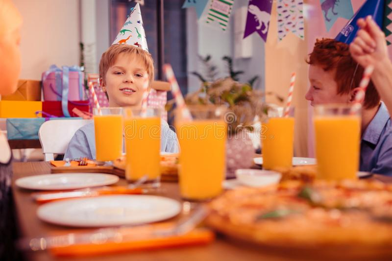 Handsome birthday boy sitting in the middle of table. Orange juice. Kind blonde child expressing positivity while waiting for guests royalty free stock images