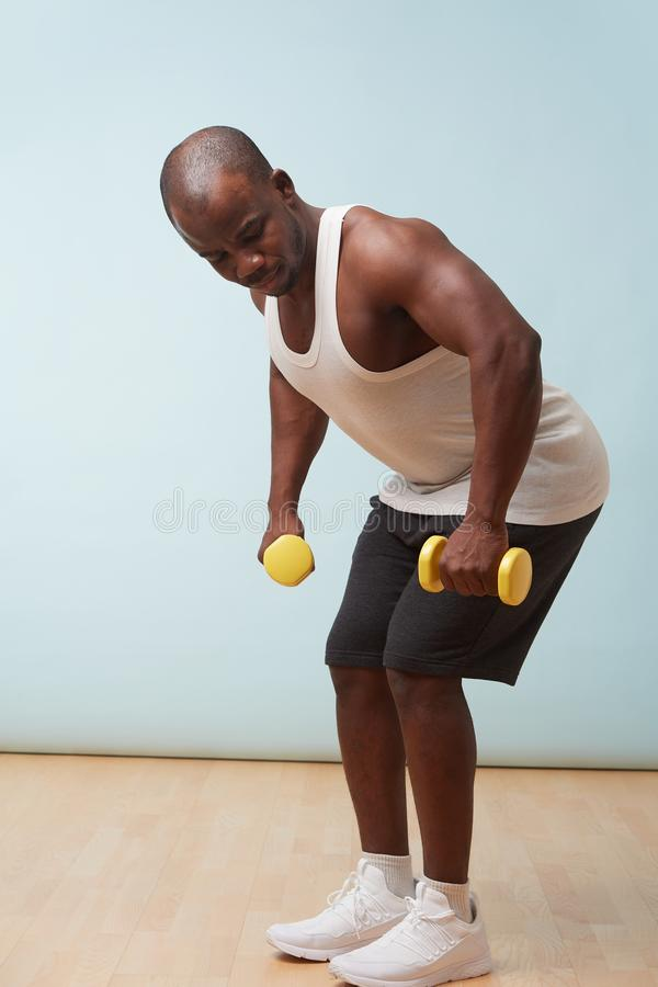 Handsome black man doing bent-over dumbbell rows. pale blue background royalty free stock photo