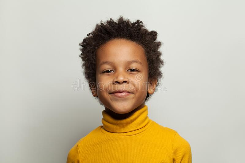 Handsome black child boy smiling and looking at camera on white background.  stock image