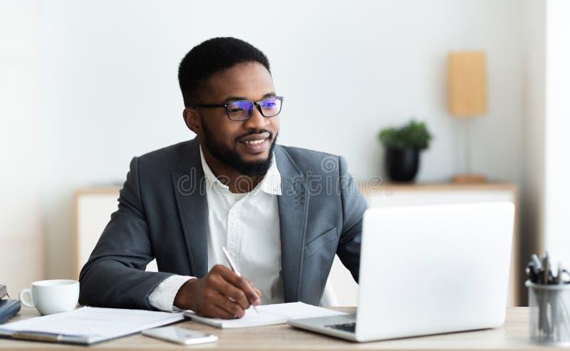 Handsome black entrepreneur working on laptop and taking notes. Handsome black entrepreneur using laptop and taking notes while working in modern white office royalty free stock photo