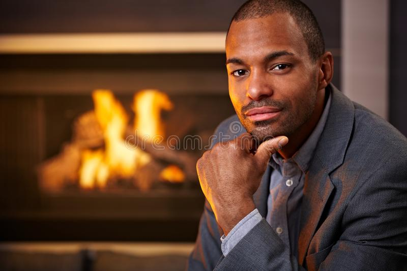 Handsome black man by fireplace royalty free stock photo