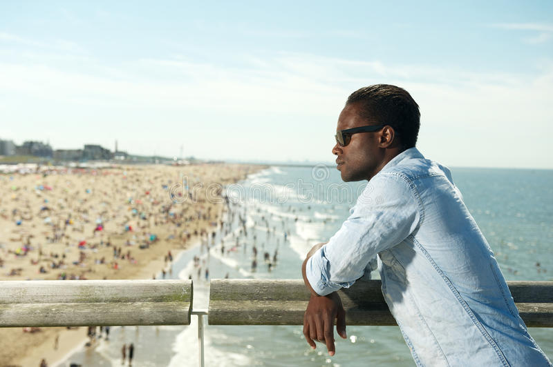 Handsome black man with sunglasses relaxing at the beach. Horizontal portrait of a handsome black man with sunglasses relaxing at the beach royalty free stock photo