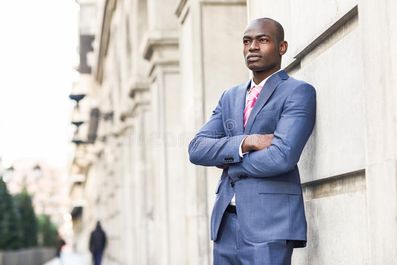 Handsome black man wearing suit in urban background royalty free stock photos