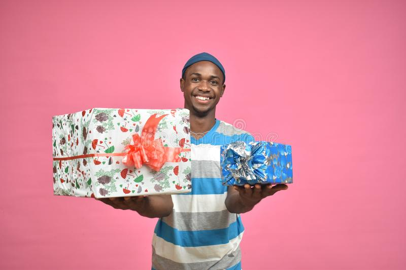 handsome black person stretching forward two gift boxes royalty free stock photos