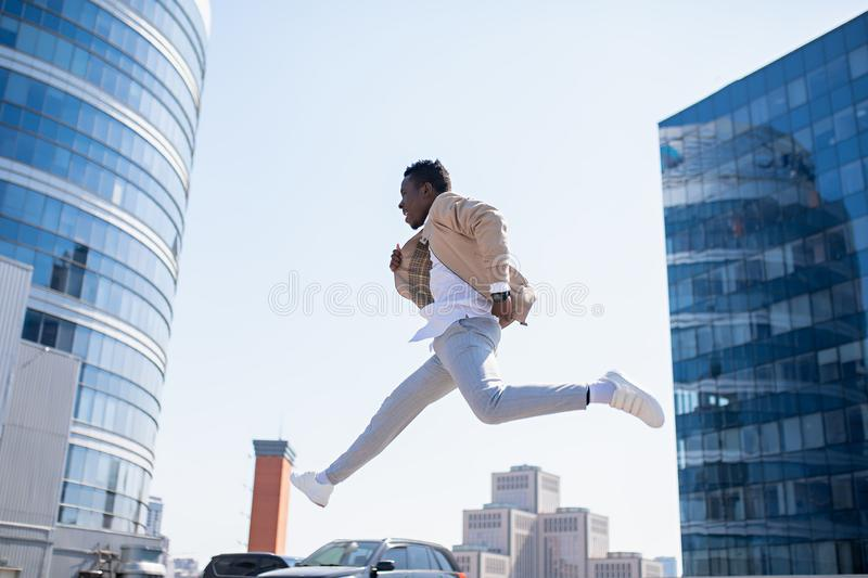 Handsome black young man in a jacket and white shirt on the street stock images