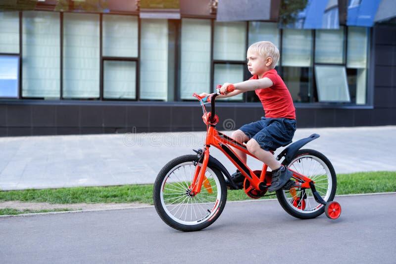 Handsome blond boy rides on a children`s bicycle. Urban background.  stock photo