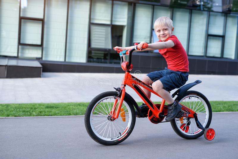Handsome blond boy rides on a children`s bicycle. Urban background.  stock photography