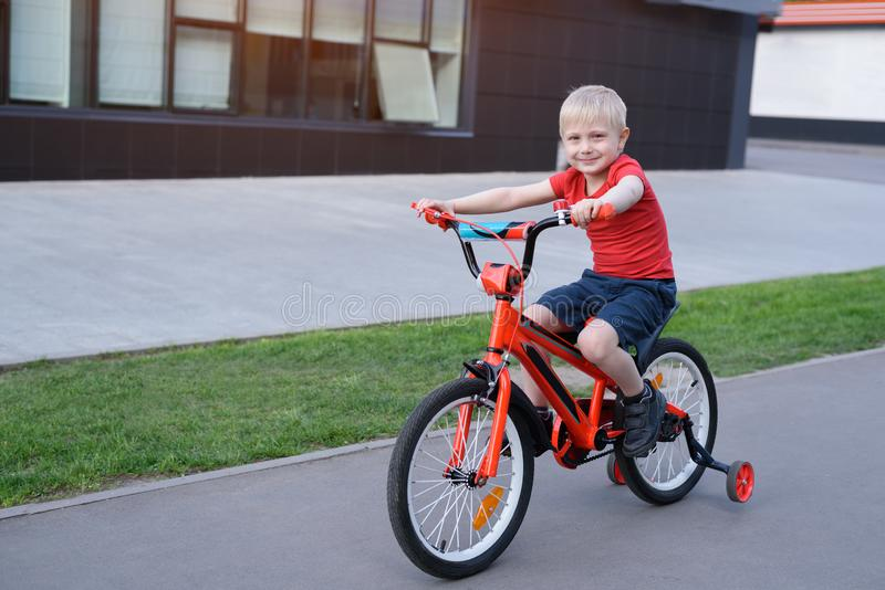 Handsome blond boy rides on a children`s bicycle. Urban background.  stock images