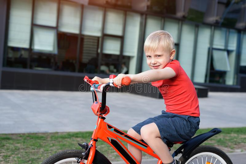 Handsome blond boy rides on a children`s bicycle. Urban background.  stock image