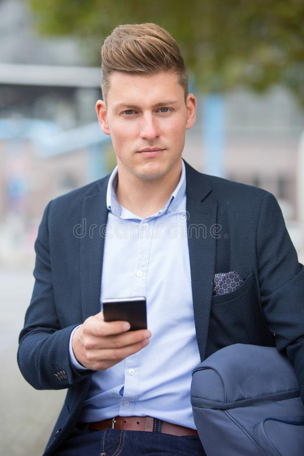 Handsome businessman sitting outside with his phone royalty free stock image