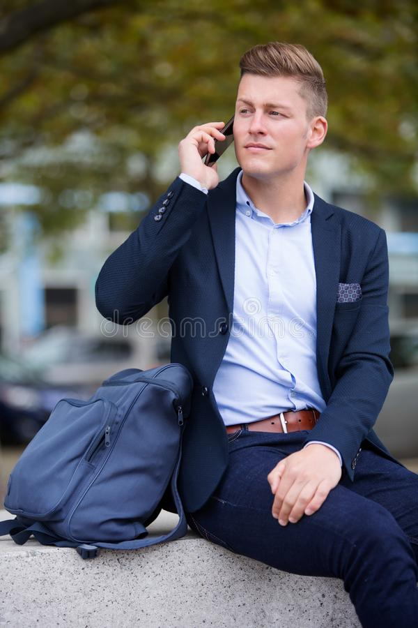 Blond businessman sitting outside and talking on the phone royalty free stock photography