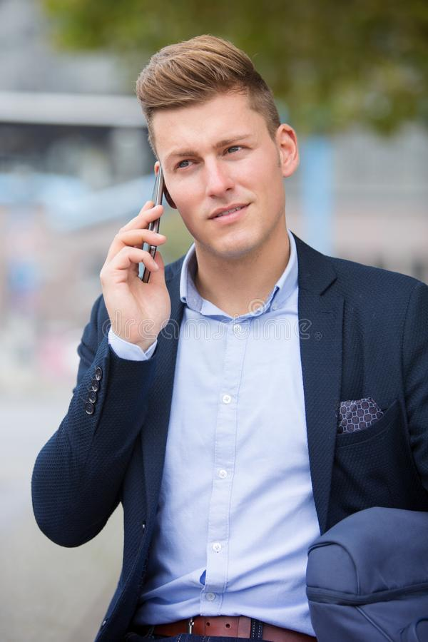 Blond businessman sitting outside and talking on the phone royalty free stock photos