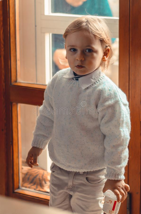 Handsome blond little boy stands near the window with yogurt in his hand stock photography