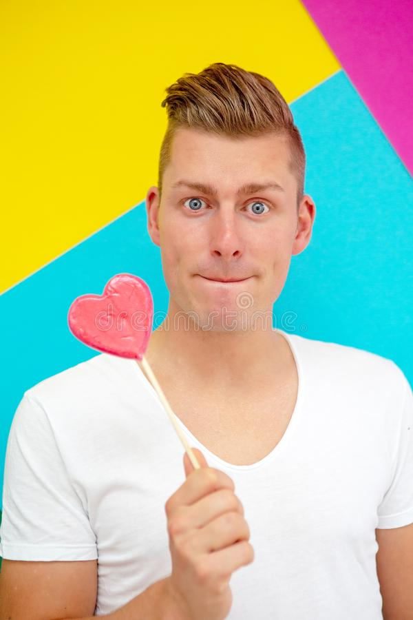 Handsome blond man holding a heart shaped lollipop royalty free stock photography