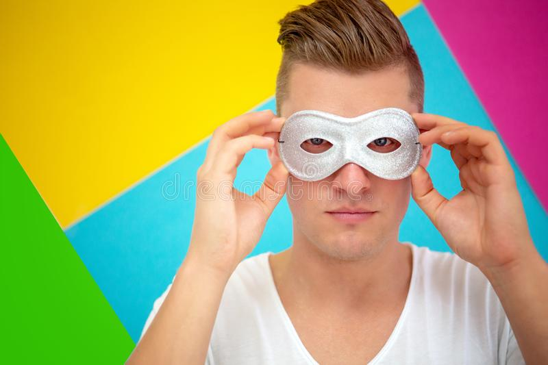 Handsome blond man wearing a silver mask stock photography