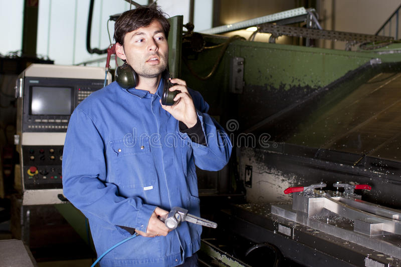 Handsome blue collar worker in factory. Blue collar worker at machine in factory stock photography