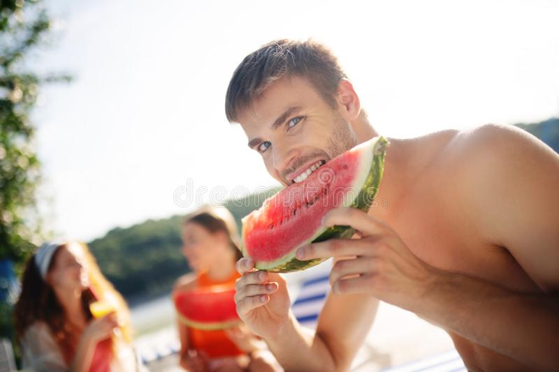 Handsome blue-eyed man eating juicy watermelon stock image