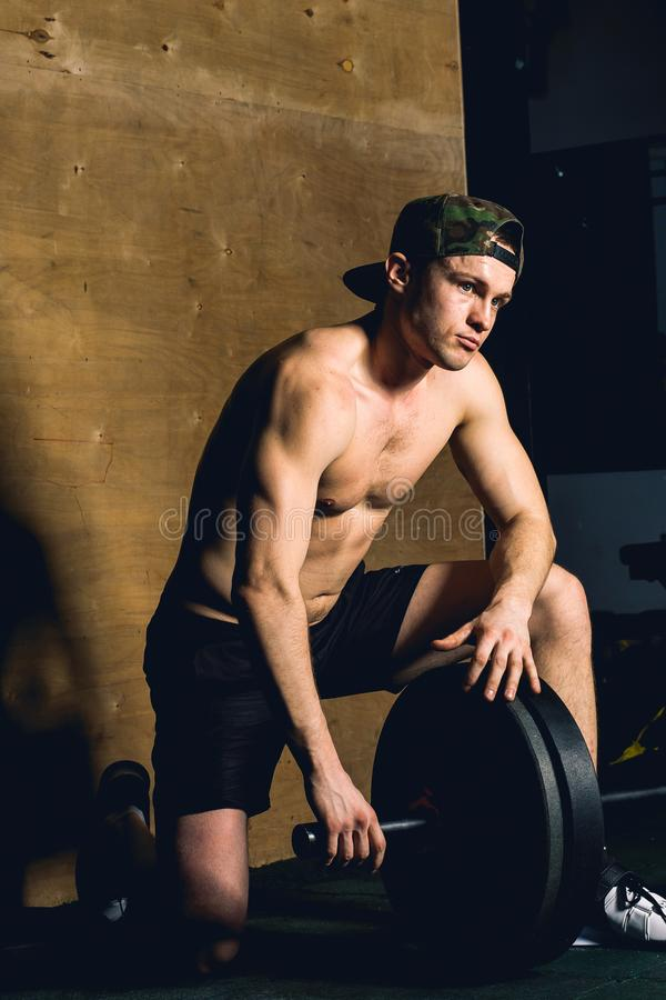 Handsome bodybuilder guy prepare to do exercises with barbell in a gym stock photos