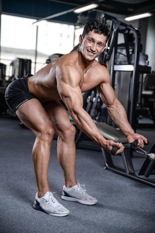 Handsome bodybuilder training in the gym man lift dumbbells. With topless body strong abs healthcare lifestyle royalty free stock photo