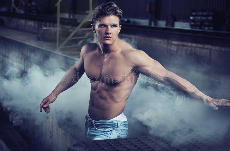 Handsome bodybuilder wearing jeans stock images
