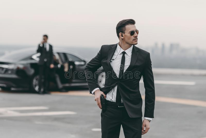 handsome bodyguard with security earpiece putting hand royalty free stock images