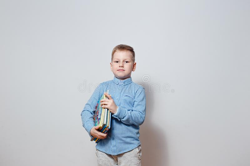 Handsome boy in a blue shirt holding the book under his arm royalty free stock photo