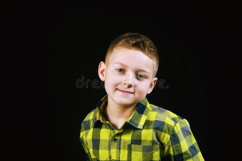 Handsome boy on a dark background in the Studio. Portrait of a handsome boy on a dark background stock images