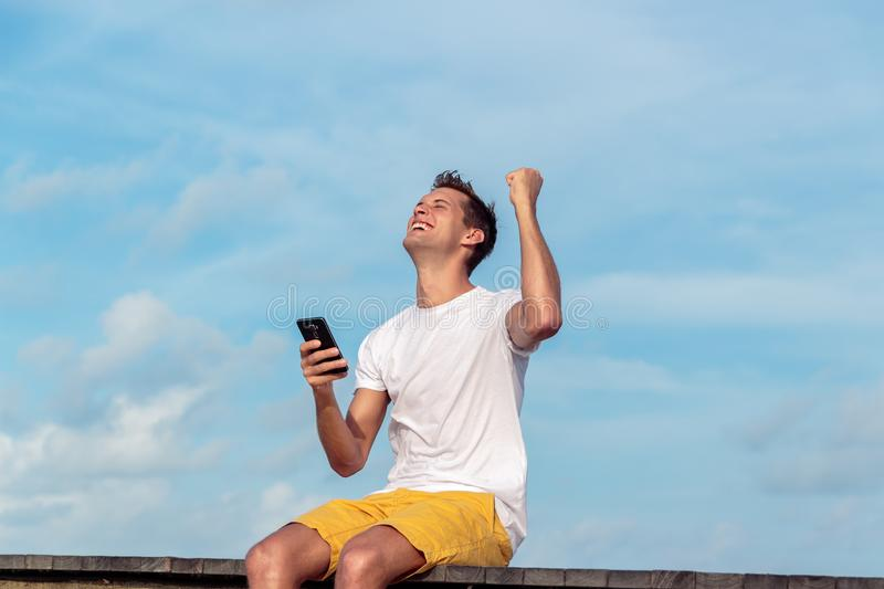 Excited man holding a smartphone and winning on line on a tropical destination. Handsome boy excited after receiving shocking news on his phone during holiday royalty free stock photos