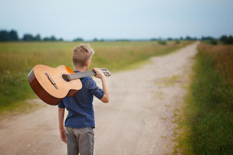 Handsome boy with guitar walking on the road in summer day. Back view royalty free stock image
