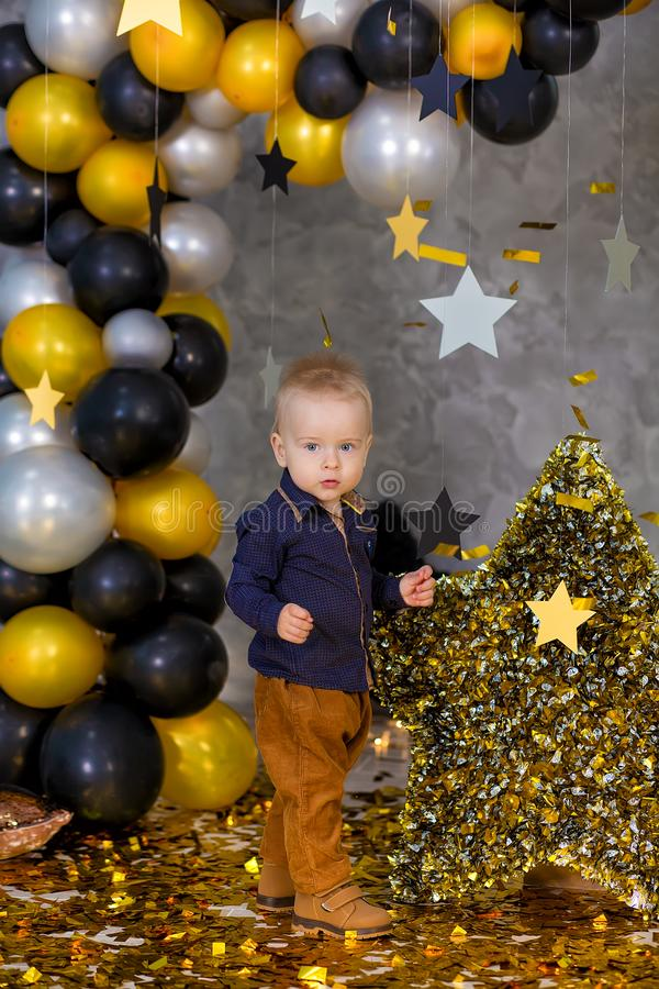 Handsome boy posing on party decorations with huge big golden star. Grey background. silver stars and different balloons stock image