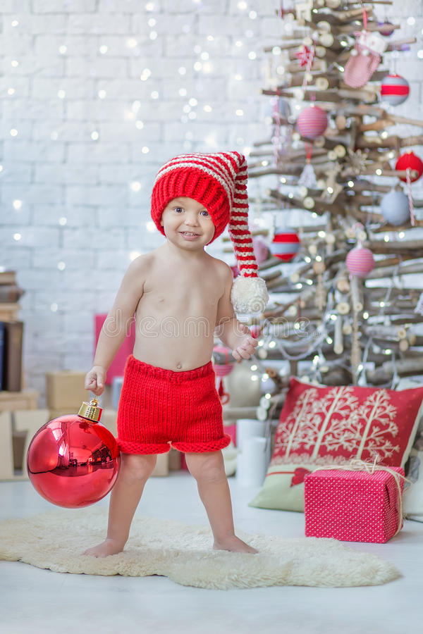 Handsome boy in red Santa Claus warm hat with big red Christmas tree toy ball celebrating New Year close to xmas tree stock photography