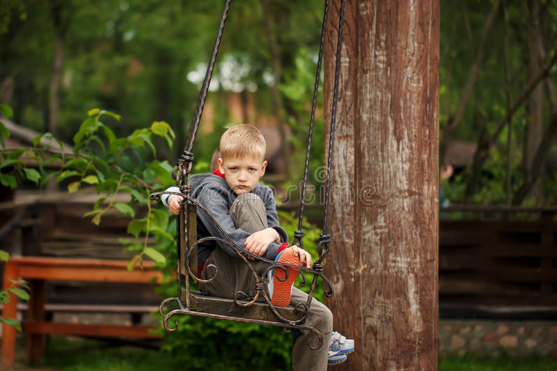 Handsome boy with a sad face sited on the bench in the summer d royalty free stock image