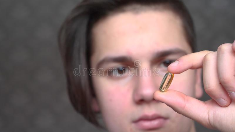 A handsome boy a teenager holds a transparent capsule medicine, pills or vitamins. And looks at it.n royalty free stock photos