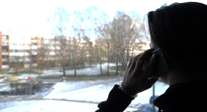 A handsome boy a teenager looks out the window to the street with a phone in his hand stock photography
