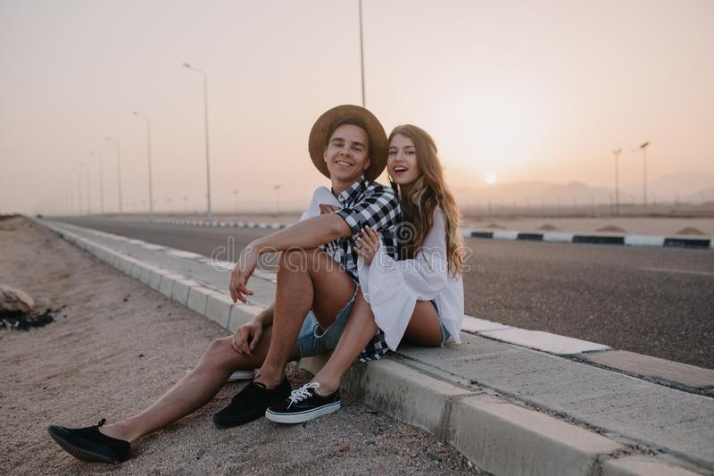 Handsome boy wearing hat and girl in white vintage blouse sitting together on the road and enjoys beauiful sunset. Charming long-haired young women resting royalty free stock photo