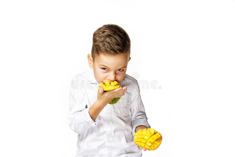 Handsome boy in a white shirt is eating a mango royalty free stock photos