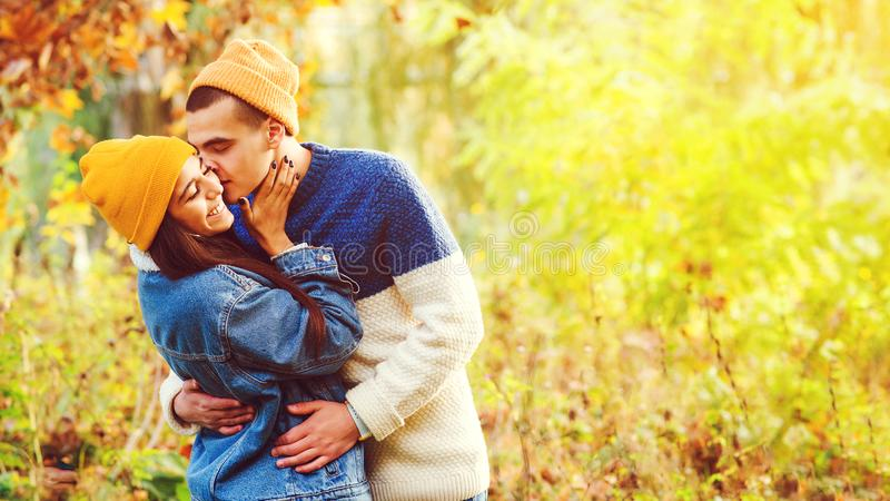 Handsome boyfriend kissing his girl in autumn park. Stylish couple enjoying relationship on nature. Couple in love. Fashion and stock photography