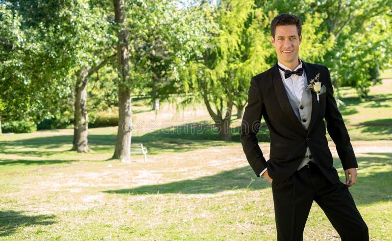Handsome bridegroom standing in garden stock photography